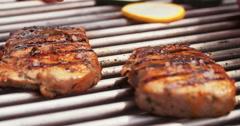 Person putting salt on pork fillet on BBQ - stock footage
