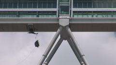 Workman hanging from bridge between Petronas Towers - stock footage