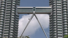 Workman hanging from bridge between Petronas Towers Stock Footage