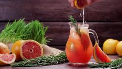 Grapefruit juice squeezed into lemonade. Jug of cold refreshing lemonade. - stock footage