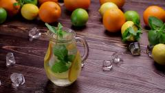 Cold citrusy lemonade in jug with ice and mint on wooden background. Stock Footage
