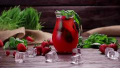 Glass jug of freshness lemonade with strawberries, cranberries and ice. Stock Footage