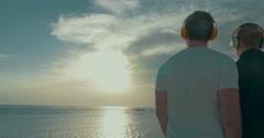 Young couple in headphones enjoying sea and sky scene Stock Footage