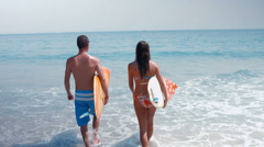 Two surfer walking on the sea with surfboard Stock Footage