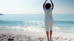 Wear view of woman doing yoga at the beach Stock Footage