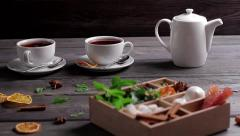 Adding sugar and mint into tea. Wooden box with mixed spices. Stock Footage