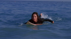 Stock Video Footage of Pretty woman paddling on a surfboard