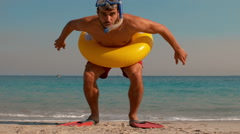 Man wearing flippers and rubber ring at the beach Stock Footage