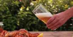 Man pouring glass of beer with chicken wings in foreground Stock Footage