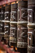Tibetan Buddhist prayer wheels in Buddhism temple. Shallow depth of field. Re Stock Photos