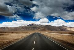 Travel forward concept background - road on plains in Himalayas with mountain - stock photo