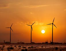 Green renewable energy concept - wind generator turbines sihouettes on sunset Stock Photos