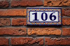 Decorated house number on brick wall in Europe. Bruges (Brugge), Belgium - stock photo