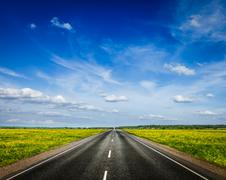 Travel concept background - road in blooming spring meadow Stock Photos