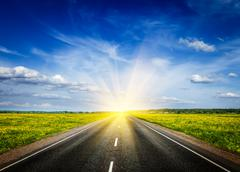 Travel concept background - road in blooming spring meadow on sunset Stock Photos