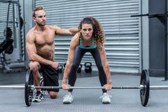 Attentive muscular woman lifting weight - stock photo