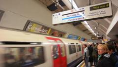 Passengers travel on London Underground platform Stock Footage