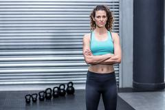 Attentive muscular woman with hands on hips Stock Photos