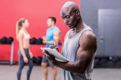 Attentive muscular trainer writing on clipboard - stock photo