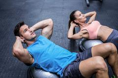 Muscular couple doing abdominal crunch - stock photo