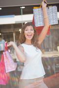 Portrait of euphoric woman raising shopping bags - stock photo