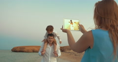 Mother with pad shooting father and son on beach Stock Footage