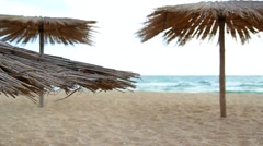 Sandy Beach With Thatched Umbrellas On A Windy Day Stock Footage