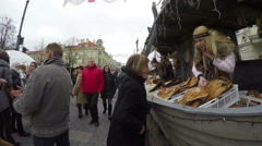 Girl offer buyer smoked fish on ship shaped kiosk. 4K Stock Footage