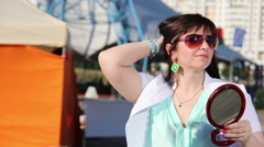 Trying on earrings at a street fair, look in the mirror Stock Footage