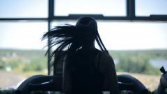 Silhouette of girl running on the treadmill and looking into the large window - stock footage