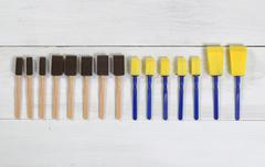 Organized new paint applicators on white wooden boards Stock Photos