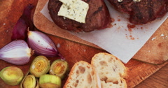 Steak medallions with baguette, herbed butter, leeks and onions Stock Footage