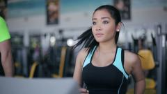 Attractive asian girl running on the treadmill in the gym Stock Footage