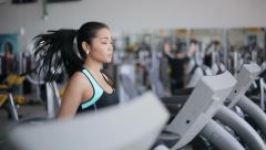 Attractive asian girl running on the treadmill in the gym - stock footage