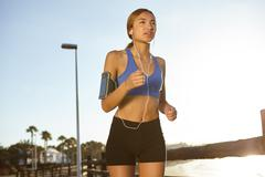 Young jogger living a healthy lifestyle by doing fitness exercises outdoors - stock photo