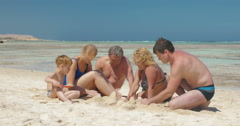 Big family building sand castle together Stock Footage