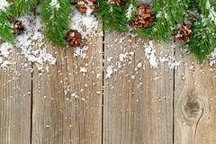 Christmas border decorations with snow on rustic wooden boards - stock photo