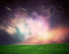 Field of grass under dream galaxy sky, space, glowing stars. - stock photo
