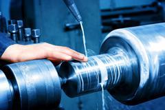 Worker measuring on industrial turning machine. Industry Kuvituskuvat