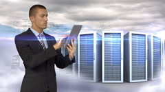 Businessman using tablet computer in front of servers towers on sky background Stock Footage