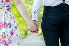 Young couple in love holding hands in summer park. Dating - stock photo