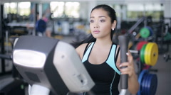 Attractive asian girl at the gym exercising on the xtrainer machine Stock Footage