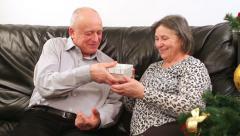 Senior couple with gift near Christmas tree - stock footage