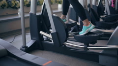 Woman at the gym exercising on the xtrainer machine Stock Footage