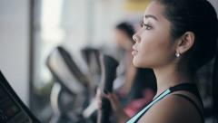 Attractive asian girl at the gym exercising on the strainer machine. Profile fac Stock Footage