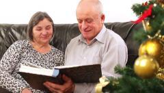 Senior couple going through photo album on Christmas 3 Stock Footage