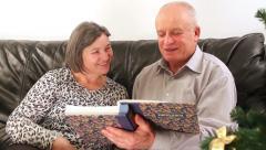 Senior couple going through photo album on Christmas  - stock footage