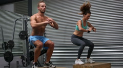 Fit couple doing set of box jumps - stock footage