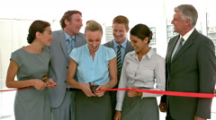 Business people cutting red band Stock Footage