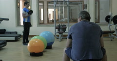 Man exercising with weight disks, his friend having a rest Stock Footage
